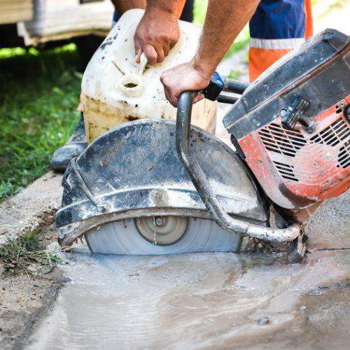 Construction worker cutting Asphalt paving for sidewalk